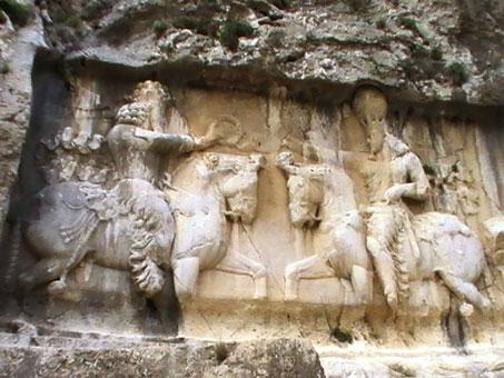 مراسم تاجگذاری شاپور یکم، فرزند اردشیر پاپکان، بنیادگذار شاهنشاهی ساسانی (۲۴۱- ۲۷۲م). در این حجاری، شاپور سوار بر اسب، تاج شاهی را از روحانی بزرگ یا مظهر اهورا مزدا که او هم سوار بر اسب است میگیرد. اردشیر بنیادگذار شاهنشاهی ساسانی در سه محل مراسم تاجگذاری خود را نقش کرده که یکی در نقش رجب، دومی در نقش رستم و سومی در تنگاب فیروزآباد است. عکس از شکوفه تقی، آوریل 2011.