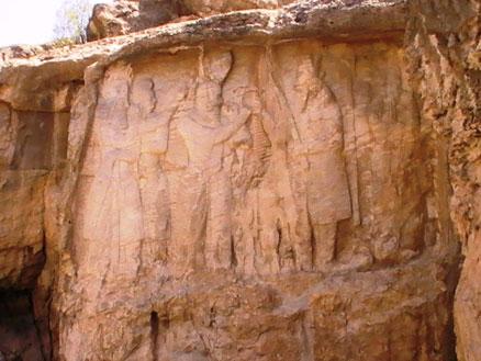 مراسم تاجگذاری اردشیر پاپکان، بنیادگذار شاهنشاهی ساسانی. این مجلس که چهار متر و نیم پهنا دارد، هشت مرد و زن و کودک را شامل میشود و چنان که معلوم است، تاج یا حلقه پادشاهی از طرف روحانی عالیمقام موبدان موبد یا مظهر اهورامزدا به شاهنشاه اعطا میشود. در پشت سر شاهنشاه دو نفر دیده میشوند که یکی از آن دو از ملازمان درباری است که مگسپرانی را بالای سر پادشاه نگاه داشته و دیگری از بزرگان کشور است که به حالت احترام ایستاده است. در برابر پادشاه و اعطای کنندۀ تاج، احتمالاً اهورامزدا یا نمایندۀ او دو کودک ایستادهاند، یکی از آنها که در جلو شاهنشاه ایستاده ممکن است شاپور، فرزند و ولیعهد او، باشد. مظهر اهورامزدا یا روحانی بزرگ با یک دست تاج را به اردشیر میدهد و با دست دیگر عصای پادشاهی را به شاهنشاه تقدیم میکند و پشت سر او، دو نفر از بانوان درباری دیده میشوند که جداگانه مراسم احترام را بجا میآورند. بیرون از این مجلس، به طرف چپ، تصویر حجاری شدۀ کرتیر است که دست راست را به حال احترام برداشته و سنگنبشتهای را نشان میدهد، این نبشته سی سطر دارد و به خط پهلوی ساسانی است که در حدود بیست سطر آن کاملاً سالم و بقیه از بین رفتهاست. سنگنبشته مربوط به کرتیر موبد موبدان، بزرگترین روحانی آن عصر، و نقش هم به ظاهر خود اوست. کرتیر در این کتیبه خدمات دینی خود را به کشور شاهنشاهی شرح داده است. عکس از شکوفه تقی، آوریل 2011.