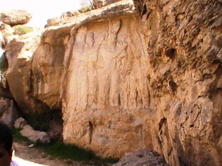 در این تصویر، کرتیر در حال ایستاده نشان داده شده است که به سنگ¬نوشته اشاره دارد. عکس از شکوفه تقی، آوریل 2011.