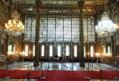 تصویر 8. تالار الماس کاخ گلستان در سمت جنوبی محوطۀ باغ گلستان بعد از عمارت بادگیر قرار دارد که از قسمتهای قدیمی و کهن ارگ سلطنتی است. این بنا به سبب آینهکاریهای داخلیاش الماس خوانده شده و شامل یک تالار بزرگ و اتاقهای گوشواره، دهلیزها، بالاخانهها و پستوهای متعدد است. زیر تالار نیز حوضخانه یا زیرزمین وسیعی وجود دارد. در سه طرف تالار، بالاتر از رفها، به سبک بناهای عهد فتحعلیشاه سه ایوانچۀ آینهکاری مقرنس و طاقنماهای باریک و کشیده ساخته شده است. عکس از مریم سجدهای.